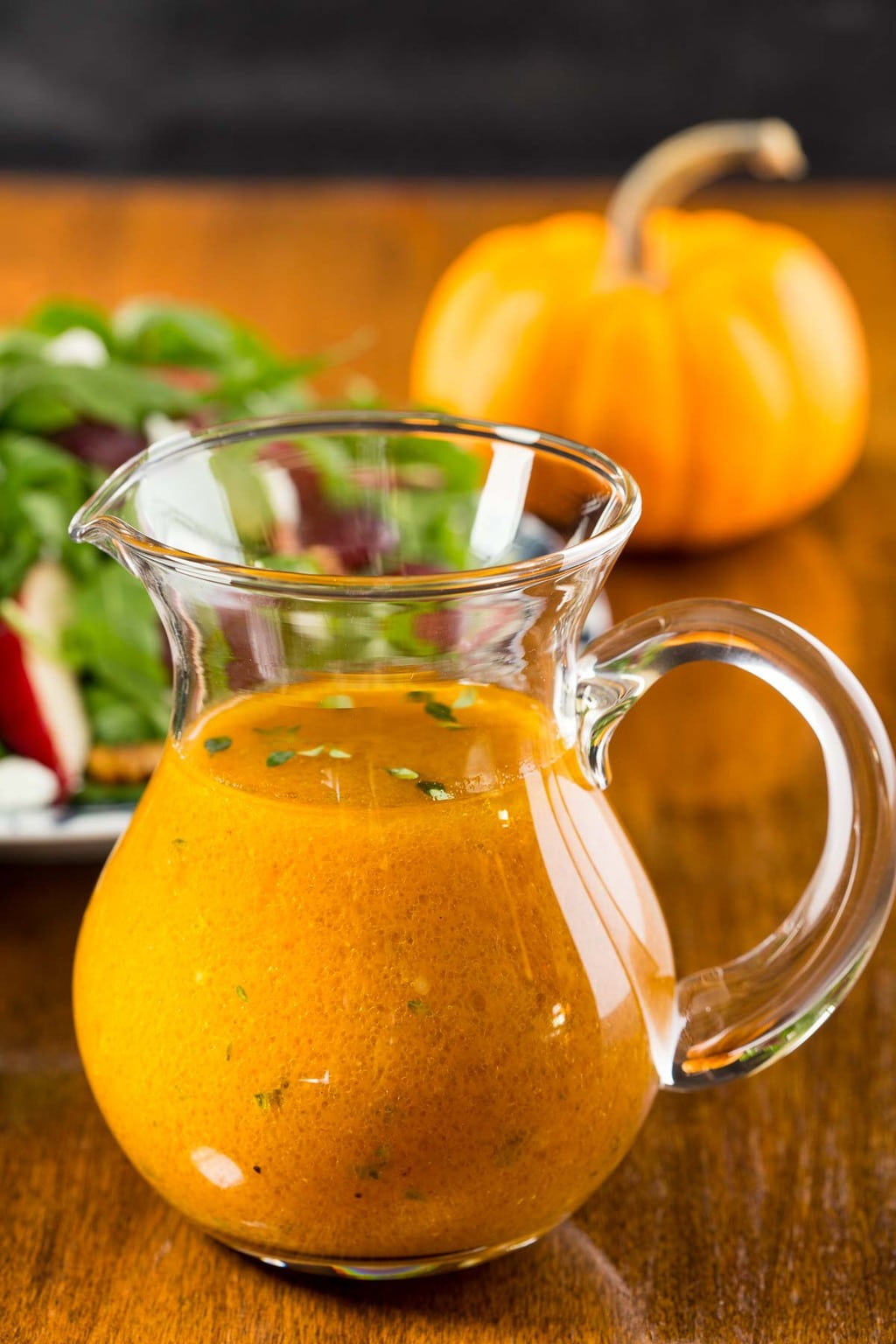 Photo of a small glass pitcher filled with Pumpkin Maple Vinaigrette. A fall apple salad and a mini pumpkin are in the background.