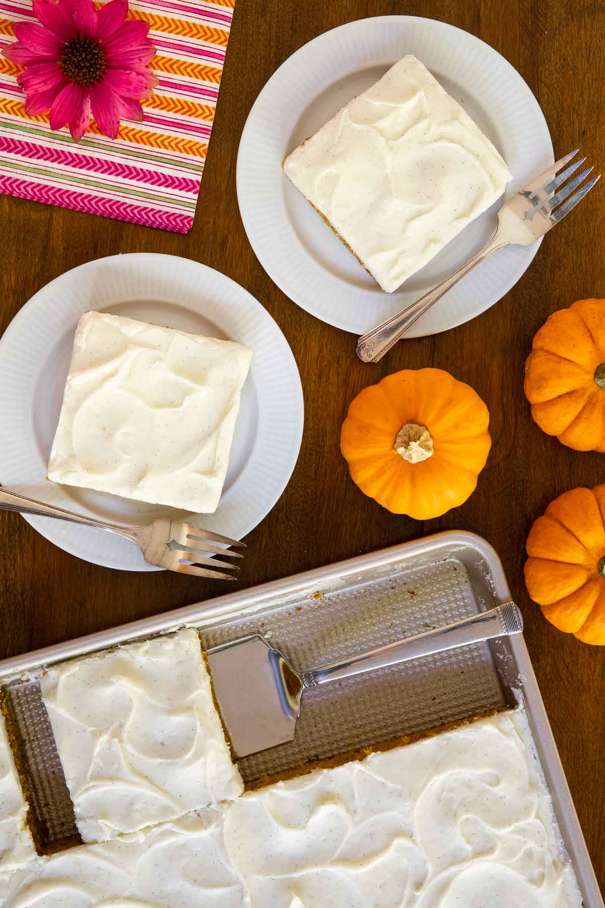 Overhead vertical photo of a One-Bowl, No-Mixer Pumpkin Sheet Cake with individual slices on serving plates next to the sheet pan.