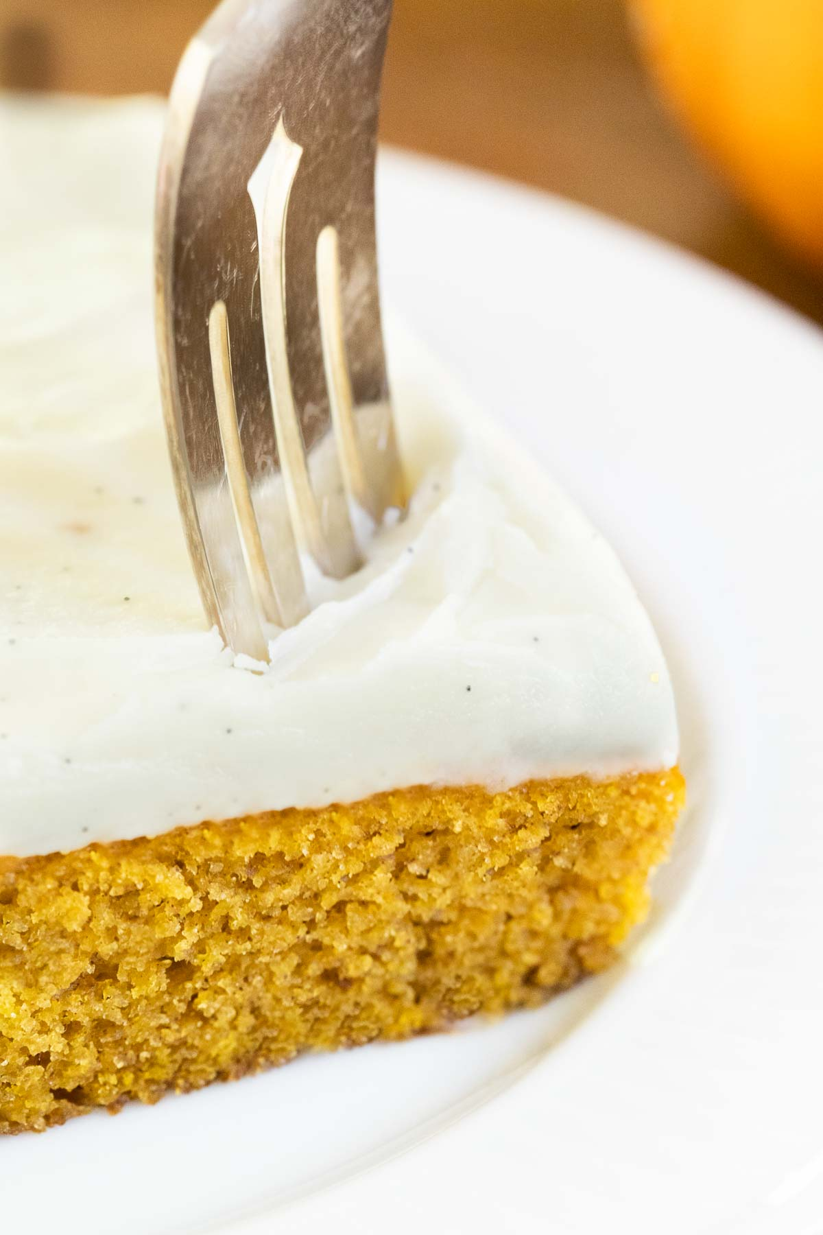 Vertical extreme closeup of a fork cutting through a slice of One-Bowl, No-Mixer Pumpkin Sheet Cake.
