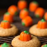 Vertical picture of Pumpkin Shortbread Cookies on a cooling rack on a black background