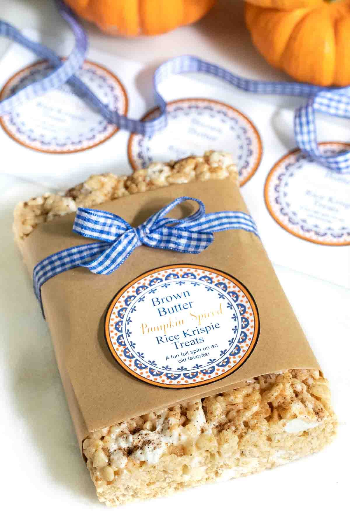 Vertical photo of Pumpkin Spiced Brown Butter Rice Krispie Treats packaged for gift giving with a custom label and wrapped in blue and white checkered ribbon.