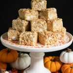 Vertical picture of pumpkin spiced brown butter rice krispie treats on a white cake stand