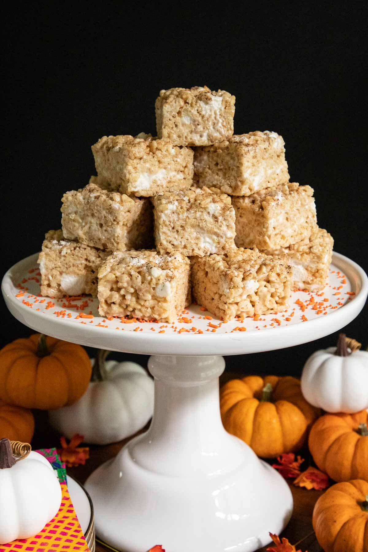 Vertical photo of Pumpkin Spiced Brown Butter Rice Krispie Treats on a white pedestal cake stand surrounded by mini pumpkins.