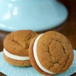 Vertical picture of two Pumpkin Whoopie Pies with Bourbon Brown Butter Buttercream on a light blue and white napkin