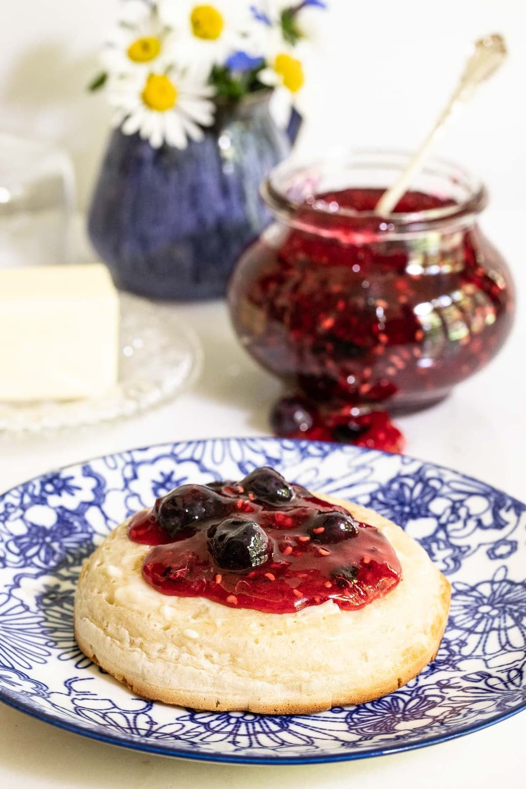 Vertical photo of a jar of Queen's Jam (Raspberry Blueberry Jam) with the jam spread on a crumpet.