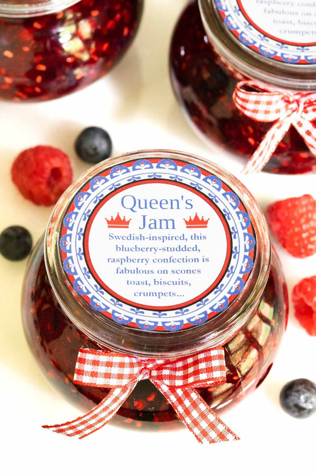 Ultra closeup vertical photo of jars of Queen's Jam (Raspberry Blueberry Jam) decorated with red and white checked ribbons.