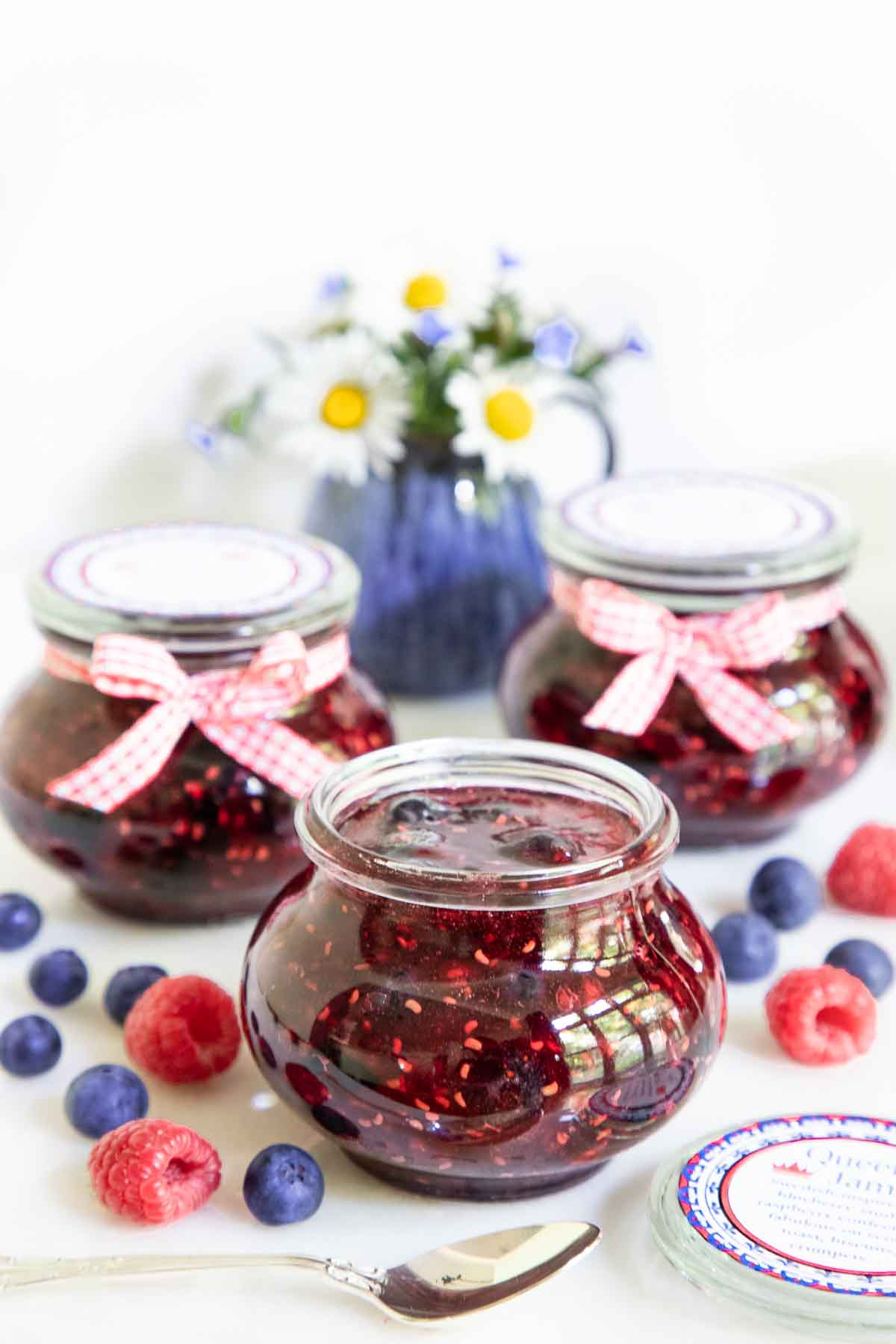 Vertical photo of a group of jars of Queen's Jam (Raspberry Blueberry Jam) with fresh flowers in the background and fresh berries in the foreground.