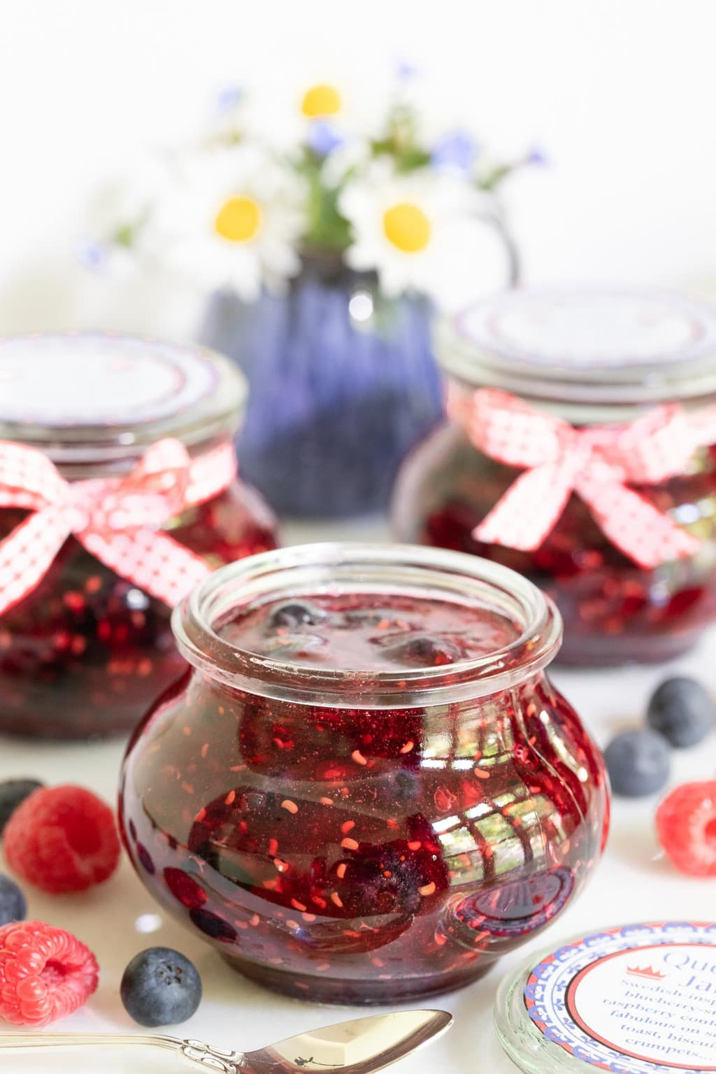 Vertical photo of jars of Queen's Jam (Raspberry Blueberry Jam) surrounded by fresh berries.
