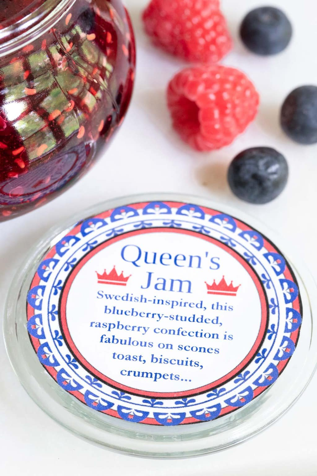 Vertical photo of the lid label for a jar of Queen's Jam (Raspberry Blueberry Jam) with fresh berries in the background.