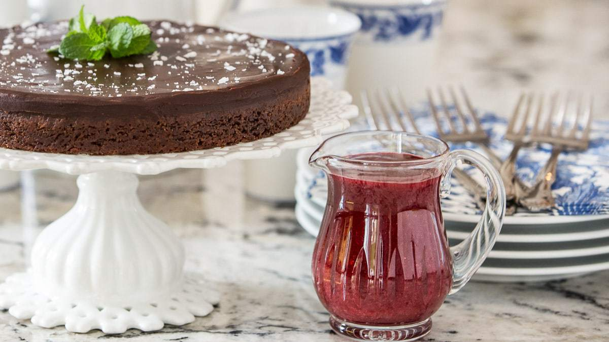 A horizontal image of a glass cruet of Raspberry Coulis next to a chocolate tart on a white cake stand