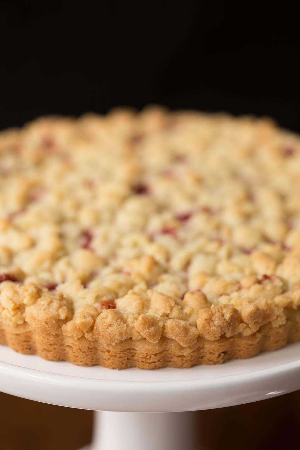 Closeup of a Raspberry Jam Shortbread Tart on a white cake pedestal.
