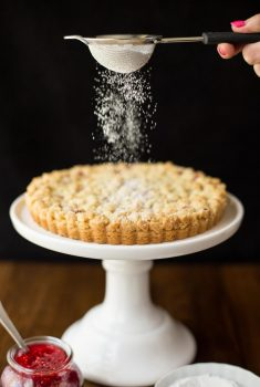 Vertical picture of raspberry jam shortbread tart on a white cake stand with powdered sugar sifted over the top