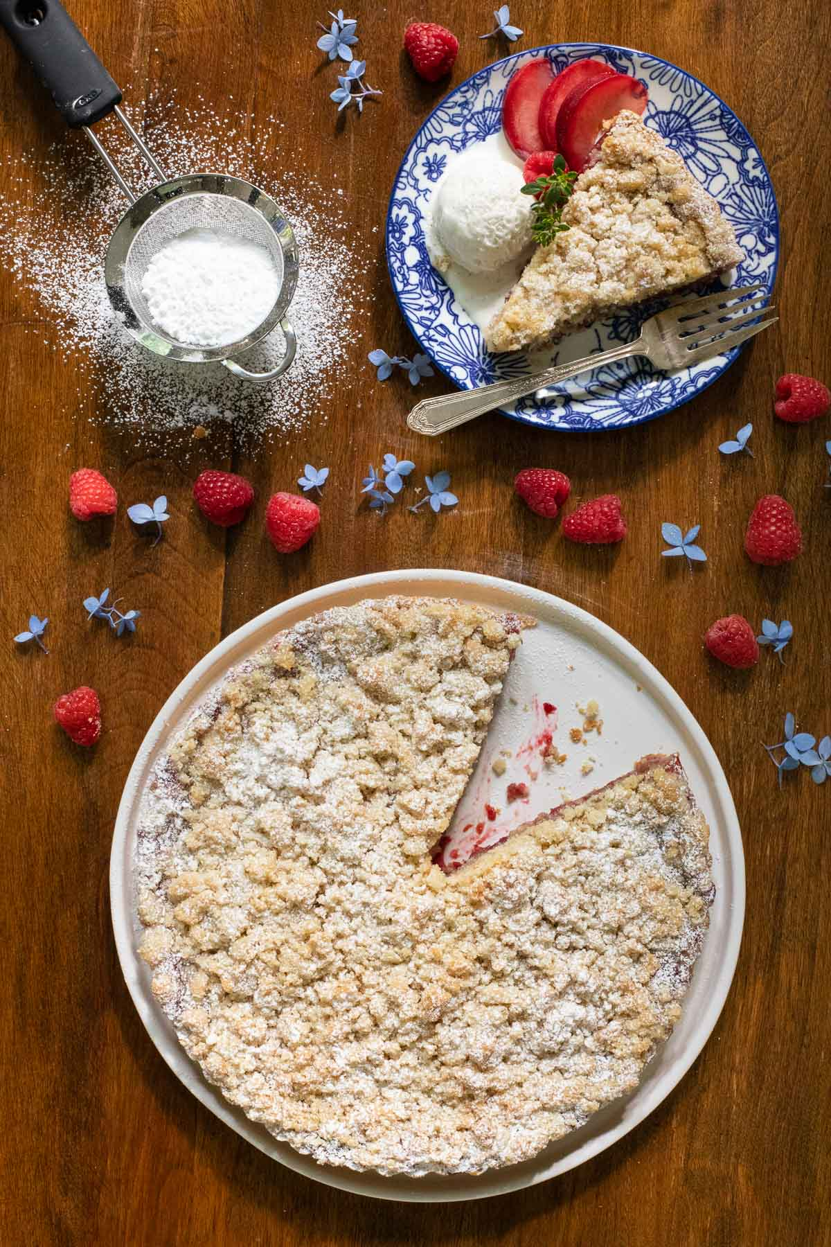 Vertical overhead photo of a Plum Raspberry Crumb Tart on a wood table with a slice of the tart on a separate plate with fresh plums, raspberries and a scoop of ice cream.