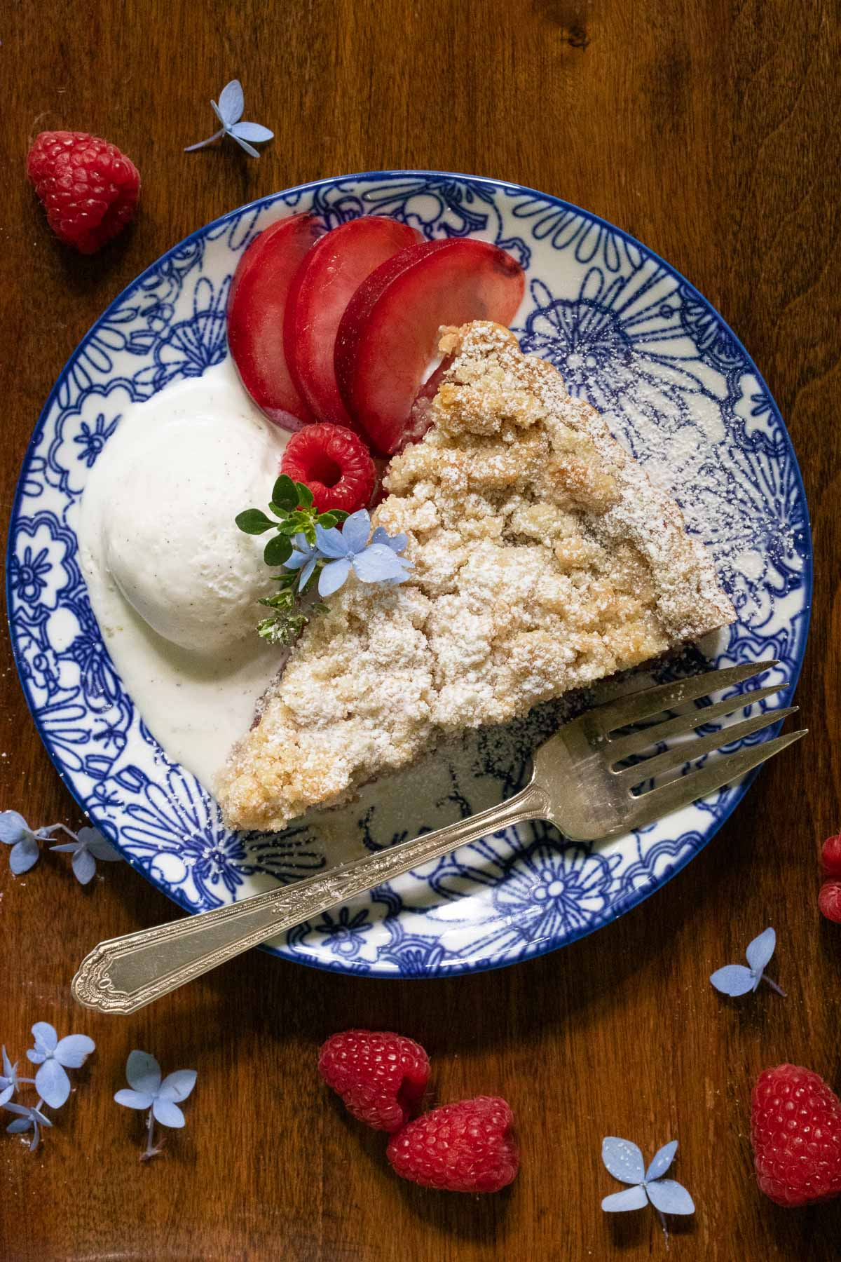 Overhead vertical photo of a slice of Plum Raspberry Crumb Tart garnished with fresh plums , raspberries and a scoop of ice cream.