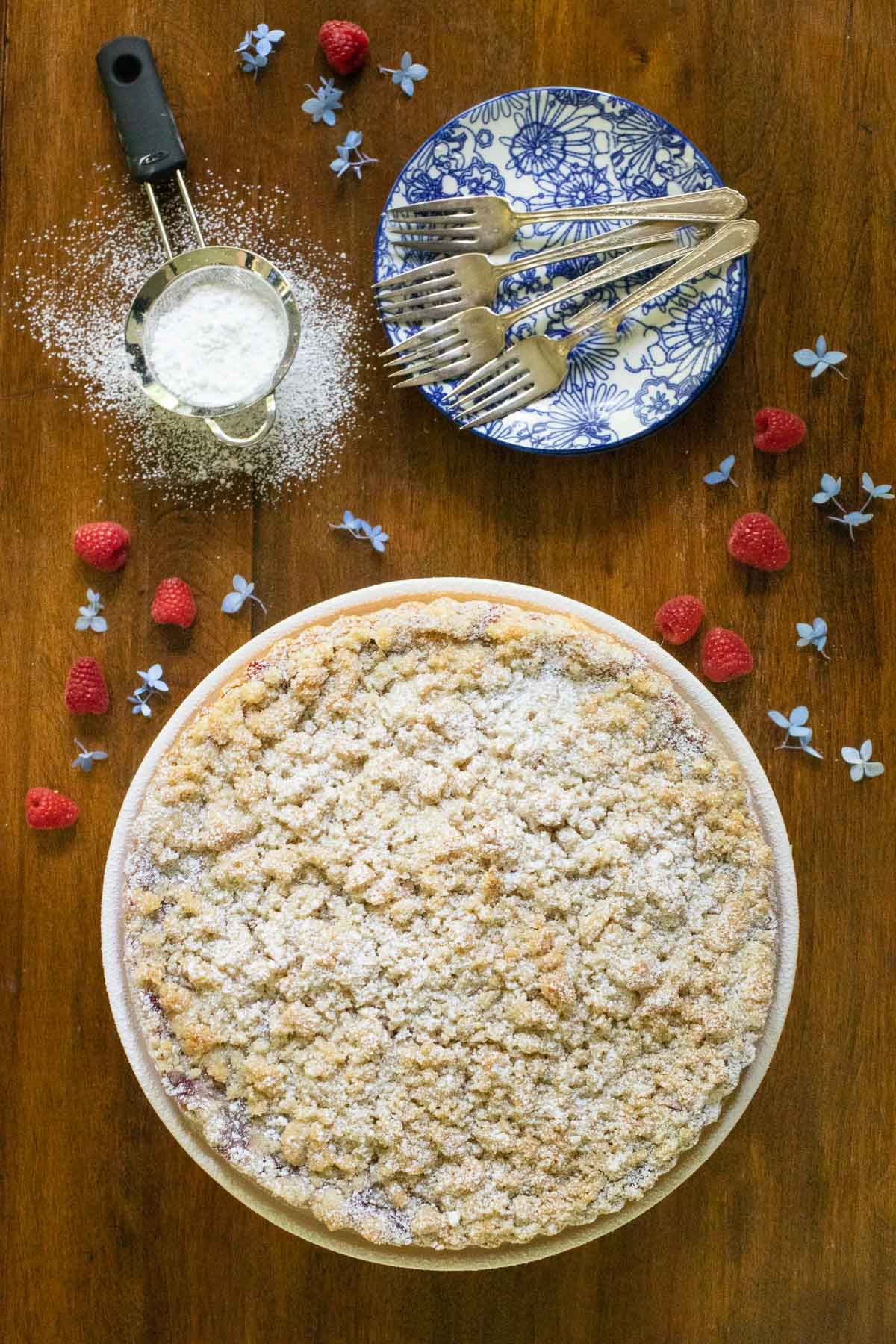 Overhead vertical photo of an Easy Plum Raspberry Crumb Tart sprinkled with powdered sugar on a wood table.