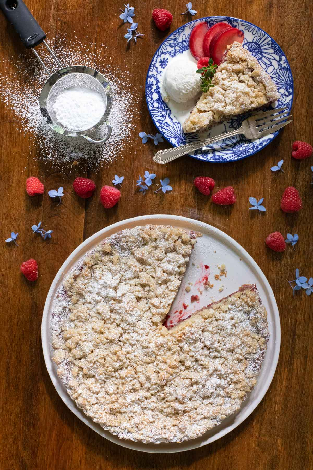 Overhead vertical photo of Raspberry Plum Crumb Tart with a slice cut out on a plate with fresh plum slices and a scoop of ice cream.