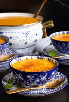 Vertical closeup photo of Red Lentil Carrot Ginger Soup in blue and white patterned bowls.