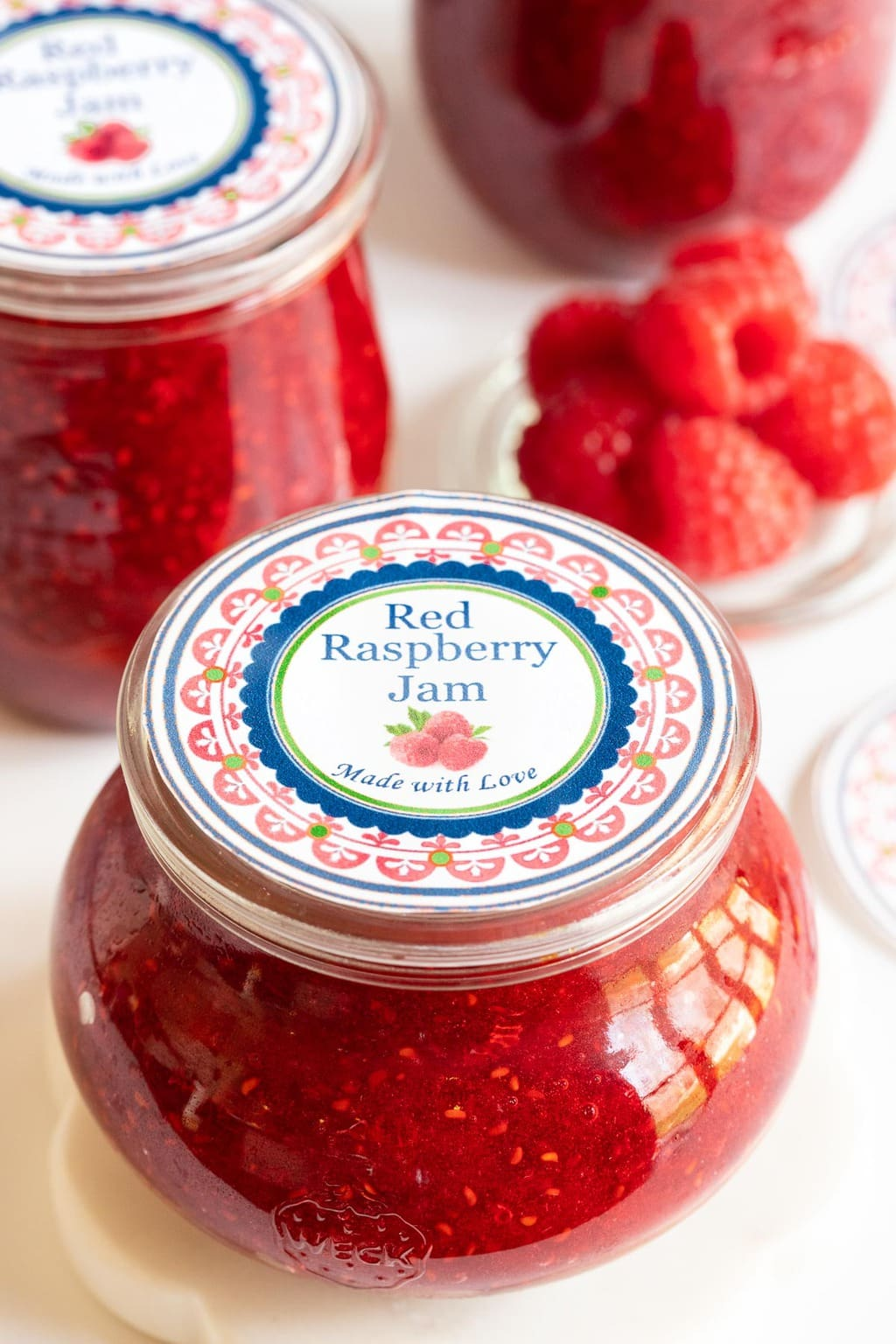 Vertical closeup photo of jars of Red Raspberry Freezer Jam with custom gift labels for the jar tops.