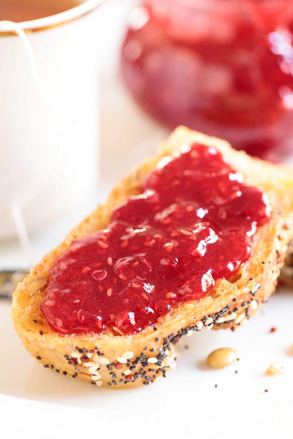 Vertical closeup photo of Easy Raspberry Freezer Jam spread on a slice of toast.