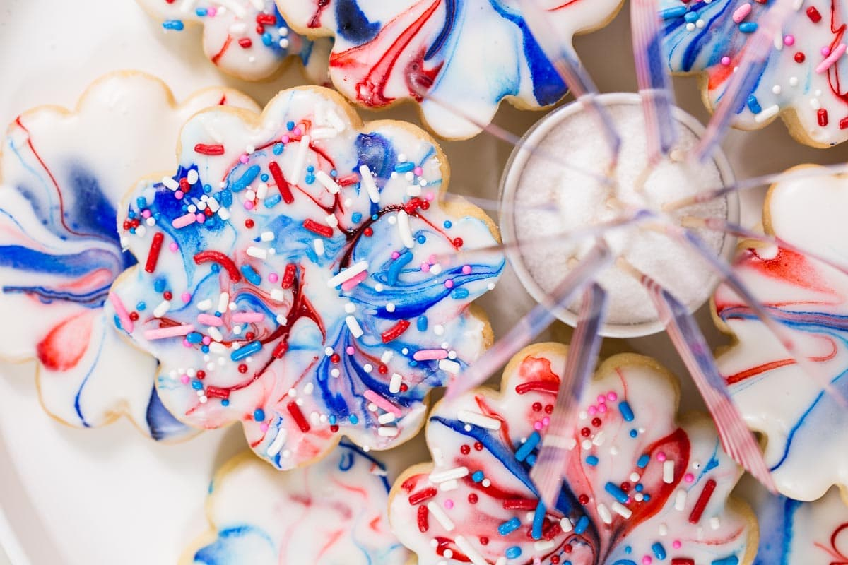 Closeup overhead photo of a plate of Red, White, and Blue Glazed Shortbread Cookies.