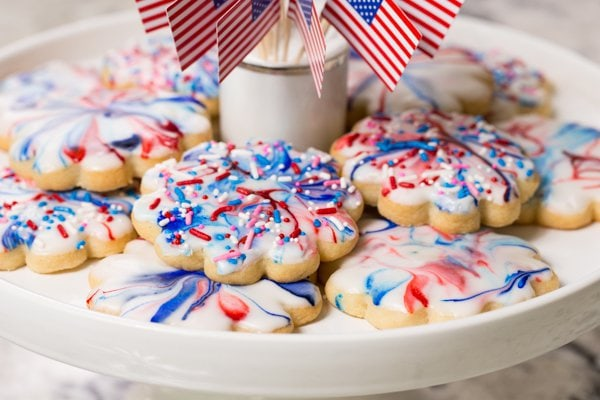 Close up photo of Red, White and Blue Glazed Shortbread Cookies on a white cake pedestal with American flags in the center.