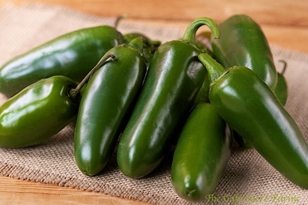 Photo of a pile of green jalapeño peppers on a tan placemat.