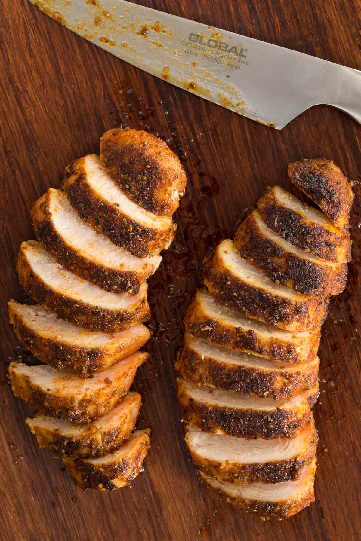 Overhead photo of two Restaurant-Style Sautéed Chicken Breasts sliced diagonally on a dark brown cutting board with a knife at the top of the photo.