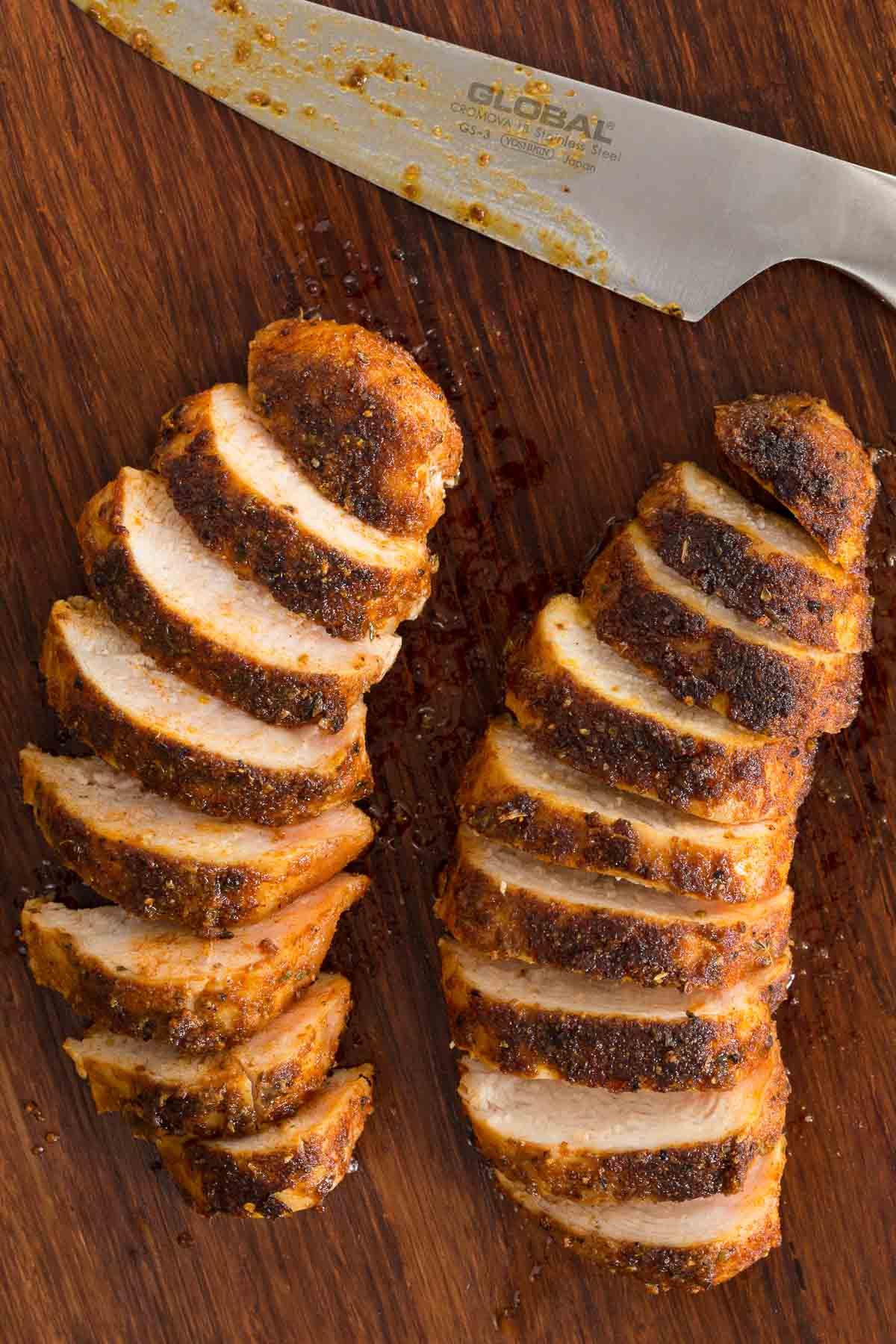 Foto aérea de dois peitos de frango salteado com estilo restaurante cortados diagonalmente em uma tábua de corte marrom escuro com uma faca na parte superior da foto.