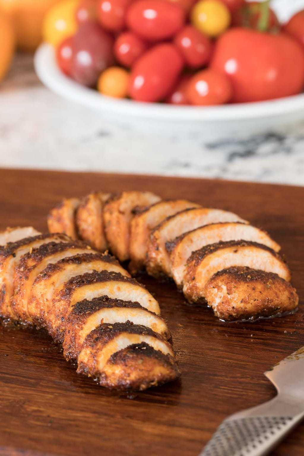 Photo of two Restaurant Style Sautéed Chicken Breasts sliced diagonally on a dark brown cutting board. A bowl of fresh tomatoes is in the background.