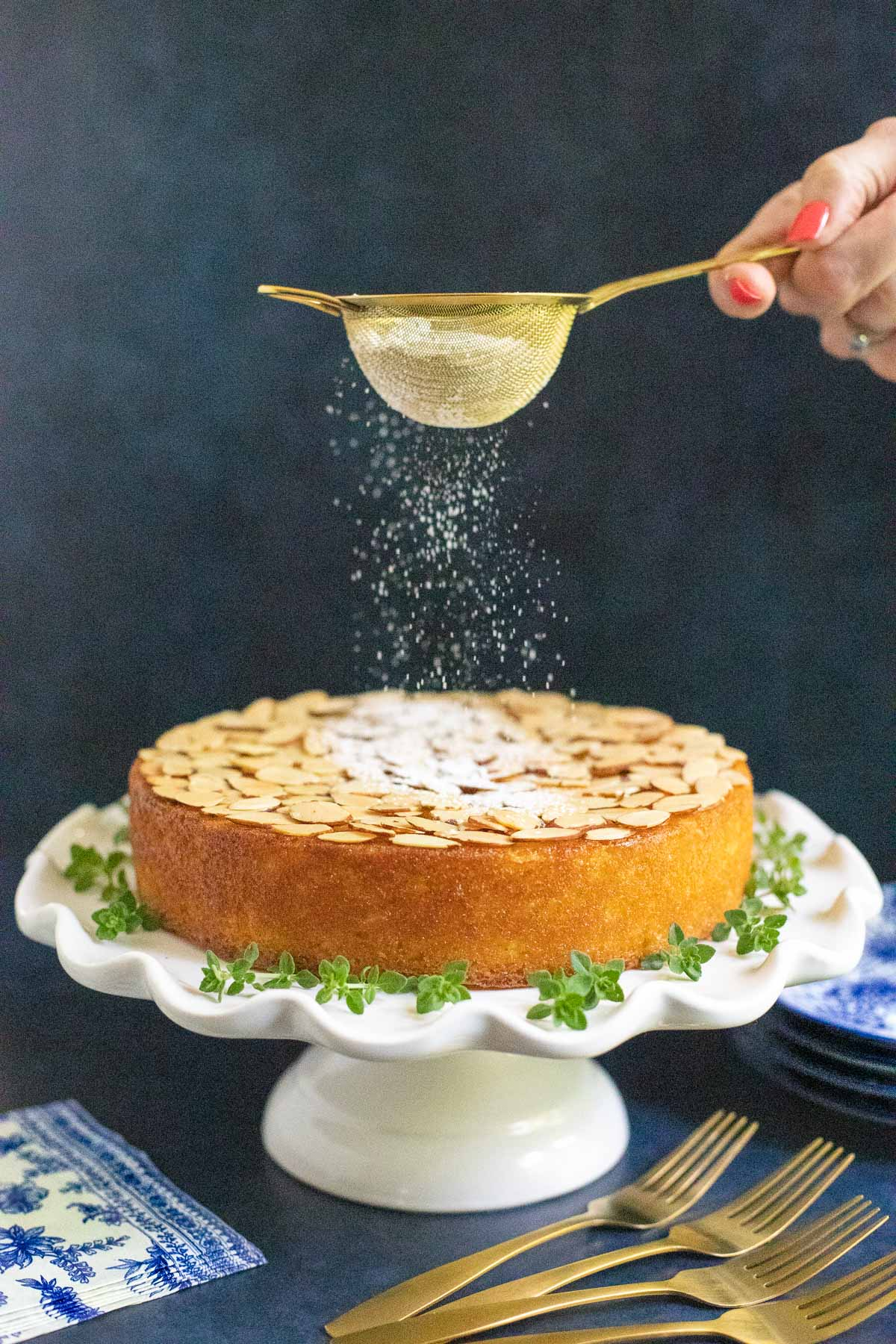Vertical photo of a hand sprinkling powdered sugar on top of a Ridiculously Easy Almond Coconut Cake on a white pedestal cake stand.