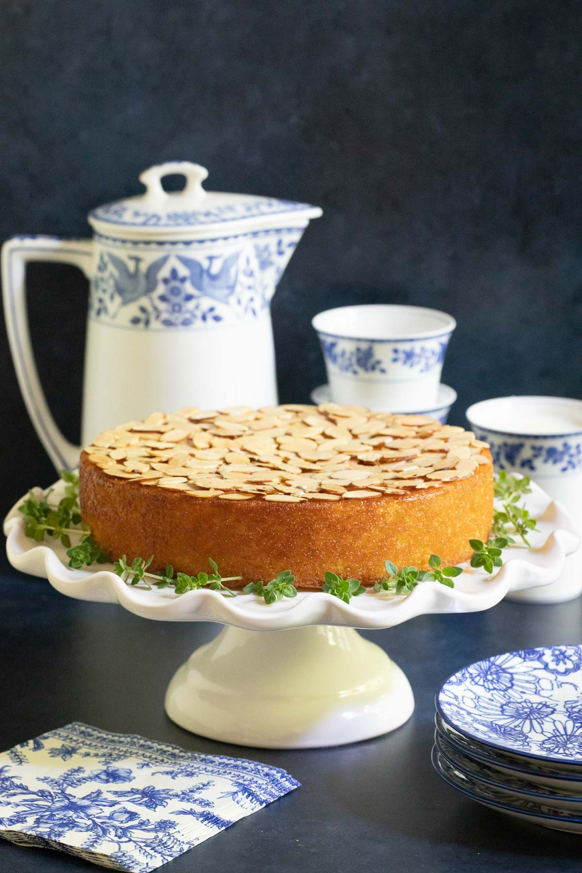 Vertical photo of a Ridiculously Easy Almond Coconut Cake on a white pedestal cake stand with a blue and white milk pitcher and cups in the background.