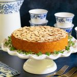 Horizontal photo of a Almond Coconut Cake on a white pedestal cake stand.