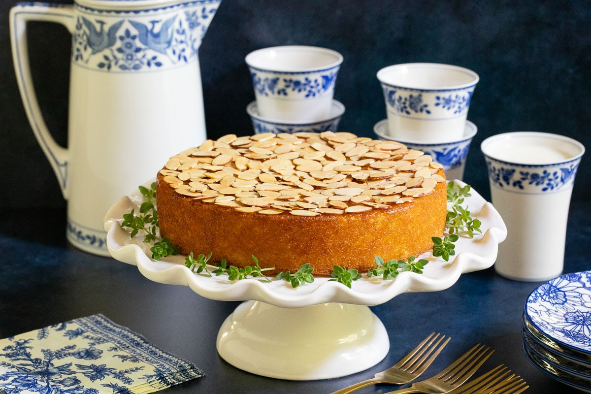 Horizontal photo of a Ridiculously Easy Almond Coconut Cake on a white pedestal cake stand with a blue and white milk pitcher and cups in the background.