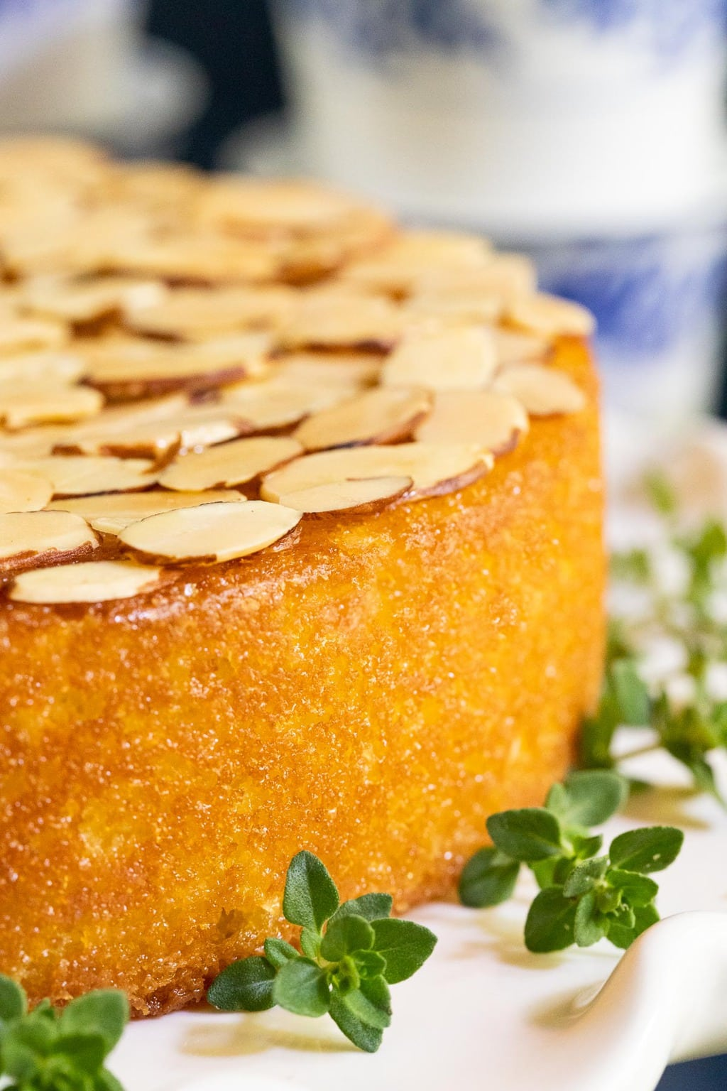Vertical extreme closeup of the side of a Ridiculously Easy Almond Coconut Cake garnished with thyme leaves.