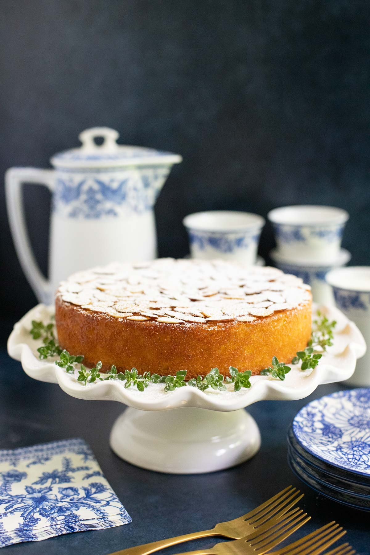 Vertical photo of a Ridiculously Easy Almond Coconut Cake on a white pedestal cake stand.