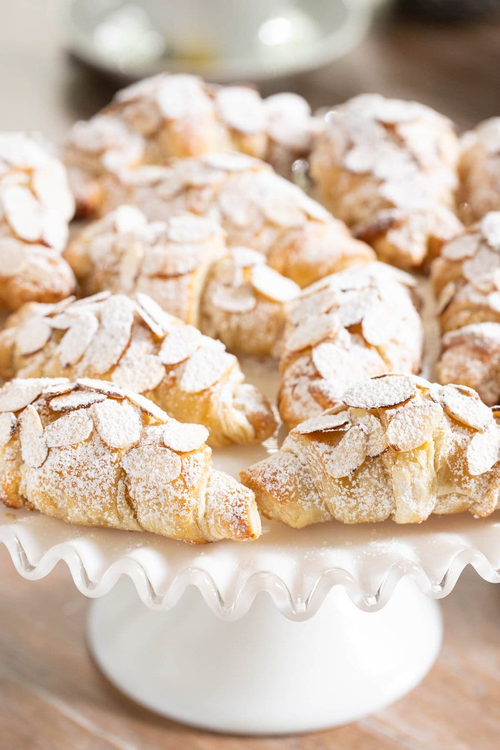 Vertical closeup photo of a batch of Ridiculously Easy Almond Croissants on a wavy white glass pedestal stand.