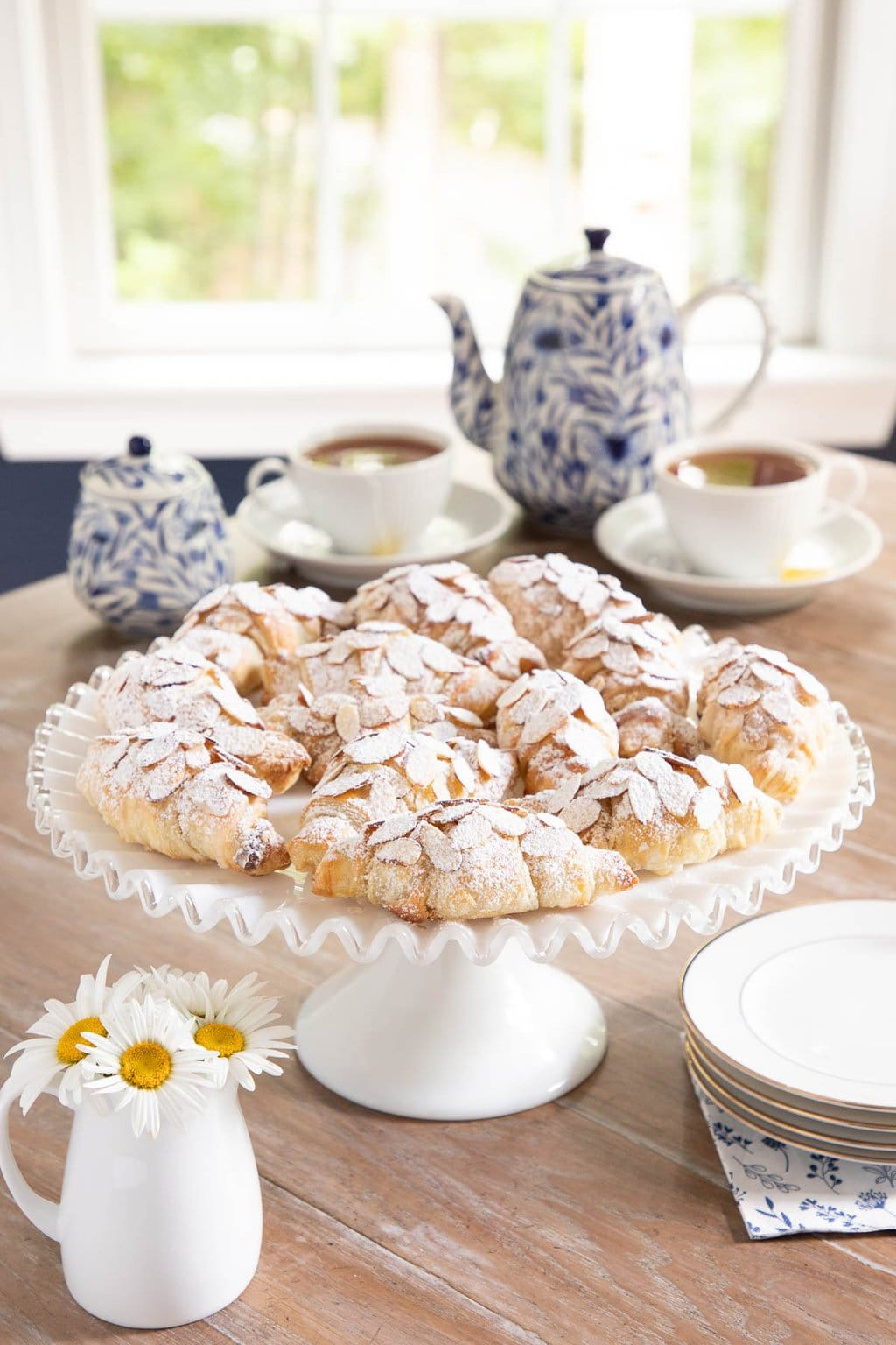 Vertical picture of easy Almond Croissants on a white cake stand with tea in the background