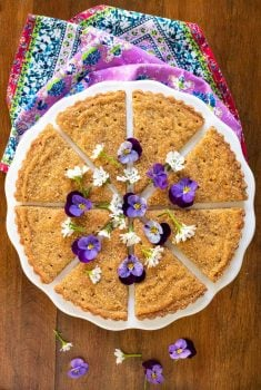 Overhead picture of Brown Sugar Shortbread cut into wedges, decorated with purple and white flowers