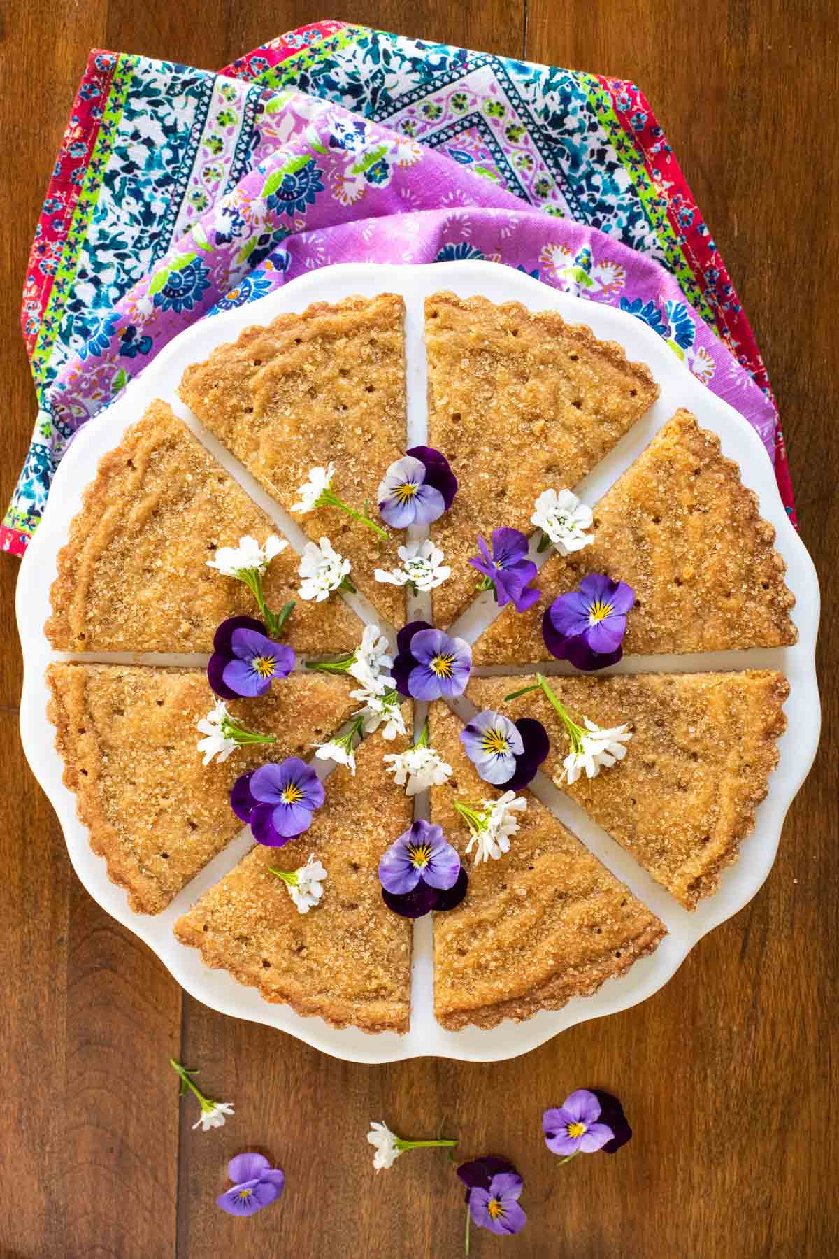 Overhead photo of Ridiculously Easy Brown Sugar Shortbread cut in wedges on a white pedestal presentation platter.