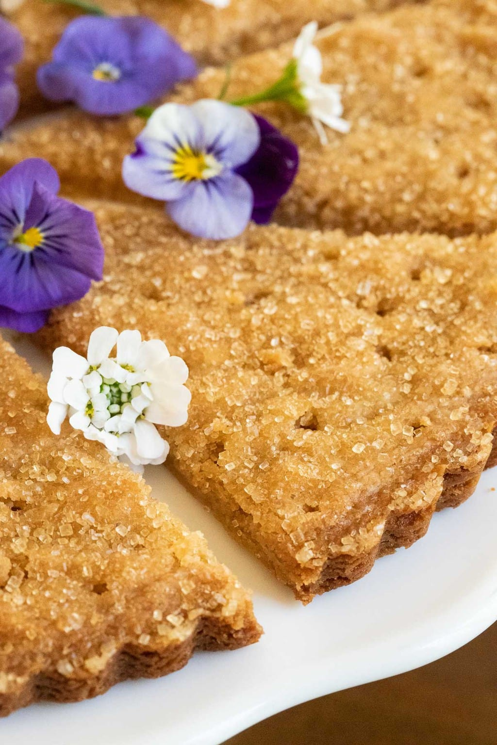 Closeup photo of wedges of Ridiculously Easy Brown Sugar Shortbread garnished with spring edible pansies.