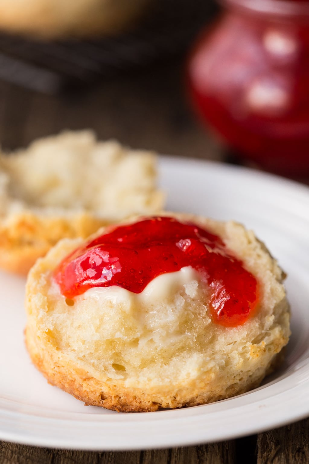 Vertical photo of a Ridiculously Easy Buttermilk Biscuits topped with melted butter and jam.