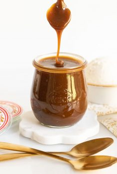 Vertical photo of a glass jar of Ridiculously Easy Butterscotch Sauce with a spoon dripping sauce back into the jar.