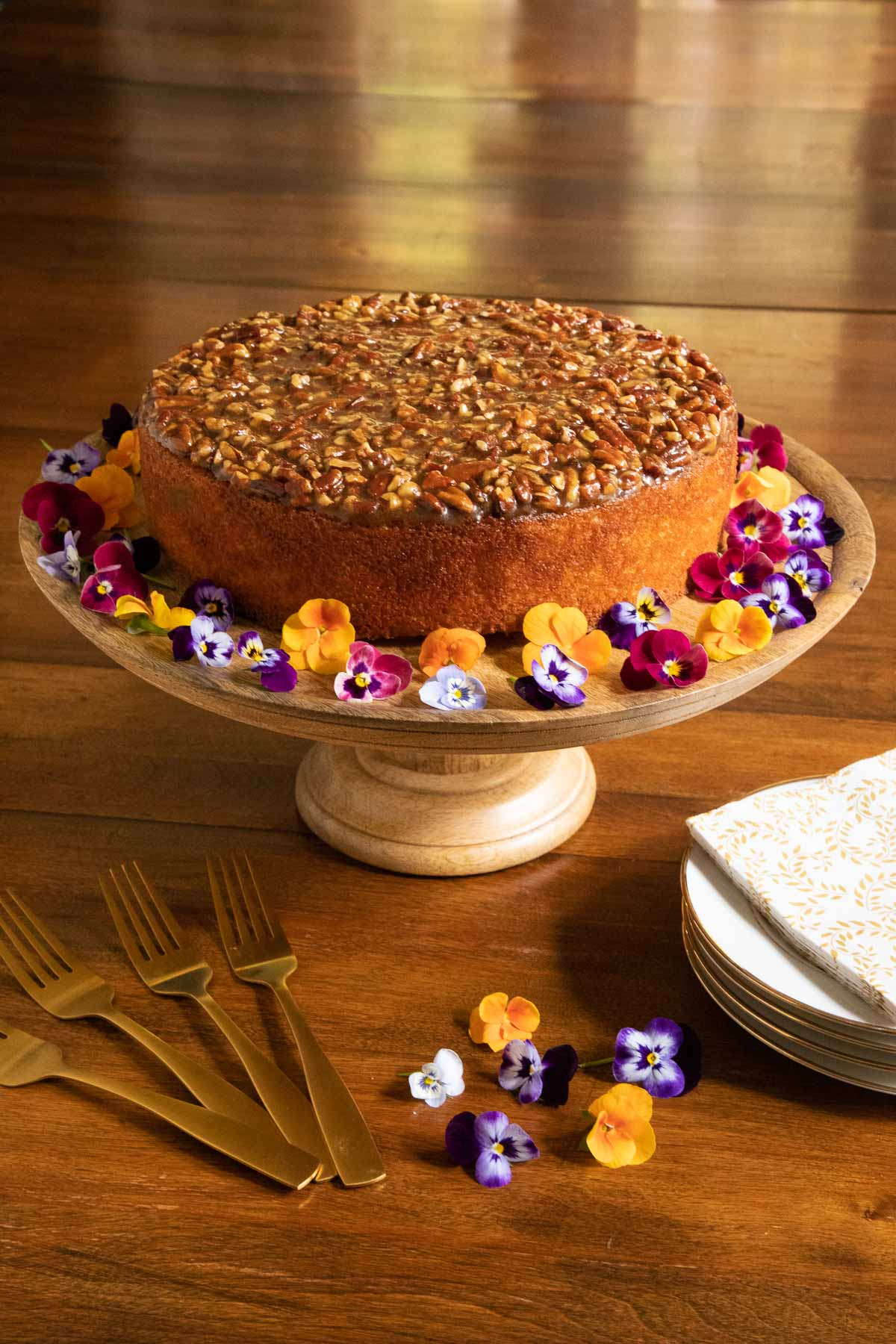 Vertical photo of a Ridiculously Easy Caramel Pecan Buttermilk Cake on a wood pedestal cake stand surrounded by mini pansy flowers.