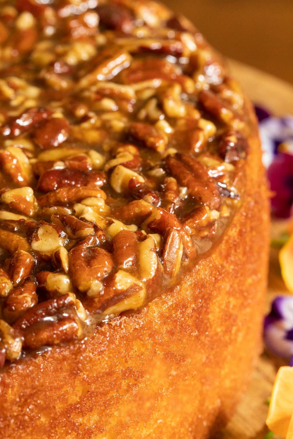 Vertical extreme closeup photo of the top and side of a Ridiculously Easy Caramel Pecan Buttermilk Cake.