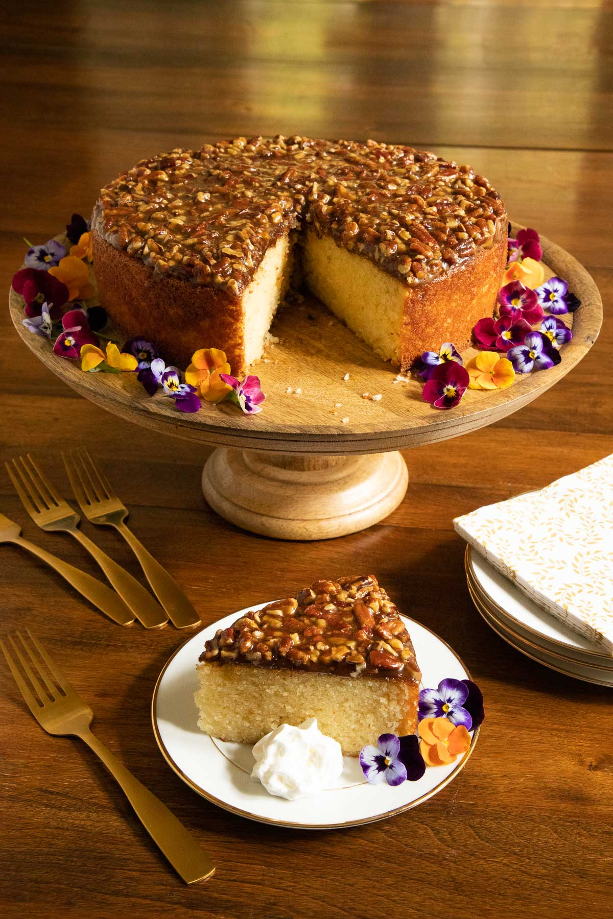 Vertical photo of a Ridiculously Easy Caramel Pecan Buttermilk Cake on a wood pedestal cake stand with a slice of the cake on a white plate in the foreground.
