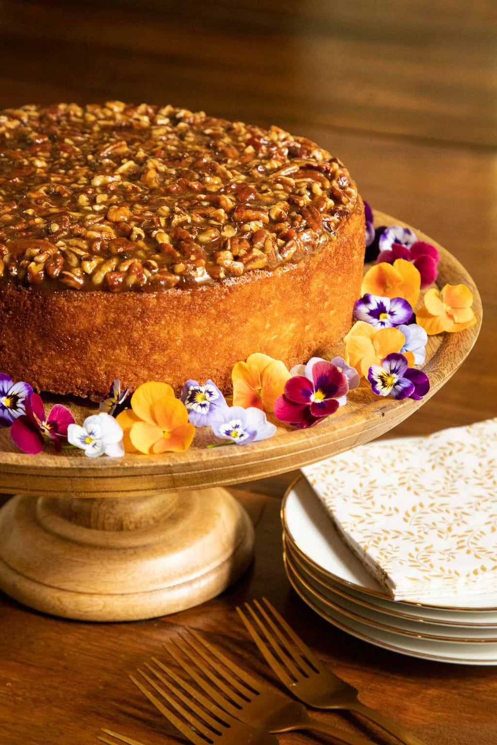 Vertical photo of a Ridiculously Easy Caramel Pecan Buttermilk Cake on a wood pedestal cake stand surrounded by mini pansies.