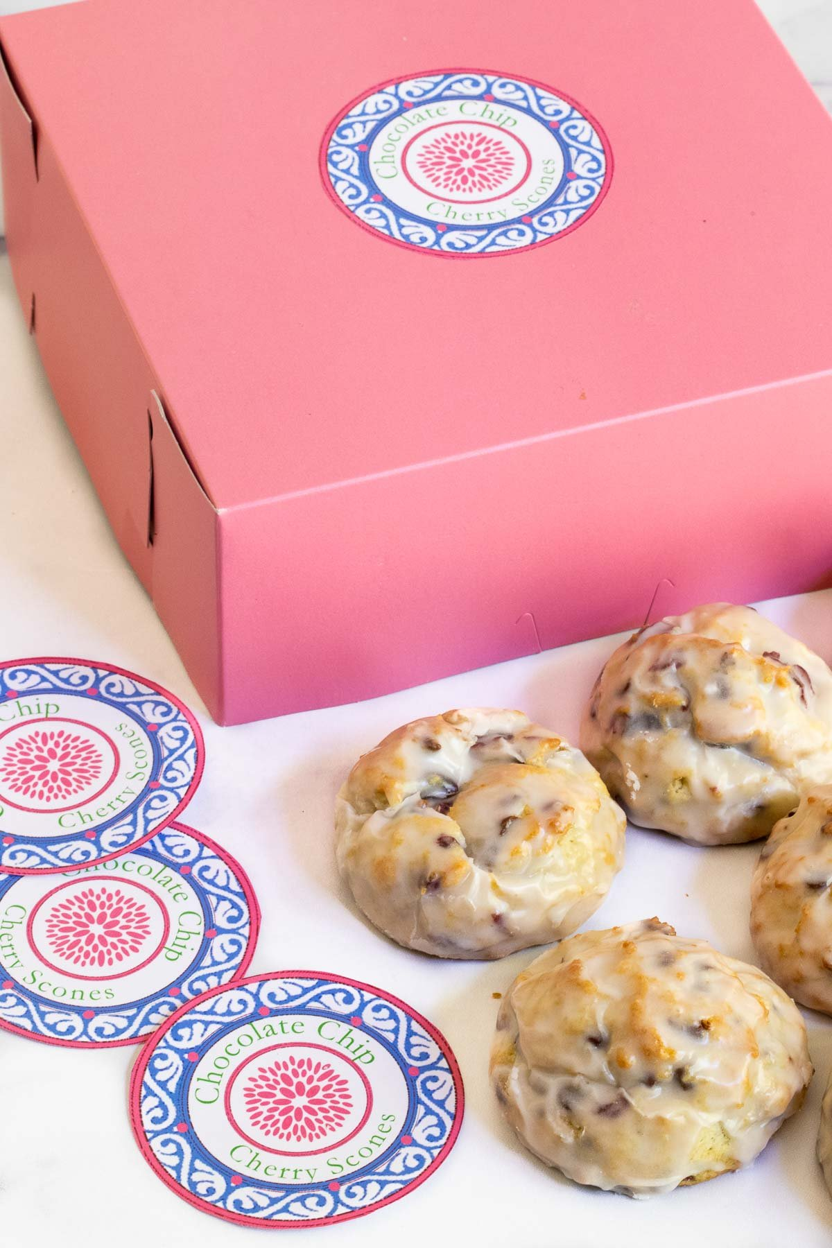 Vertical photo of a pink bakery box with custom Ridiculously Easy Chocolate Chip Scones gift labels on the box and in the foreground.