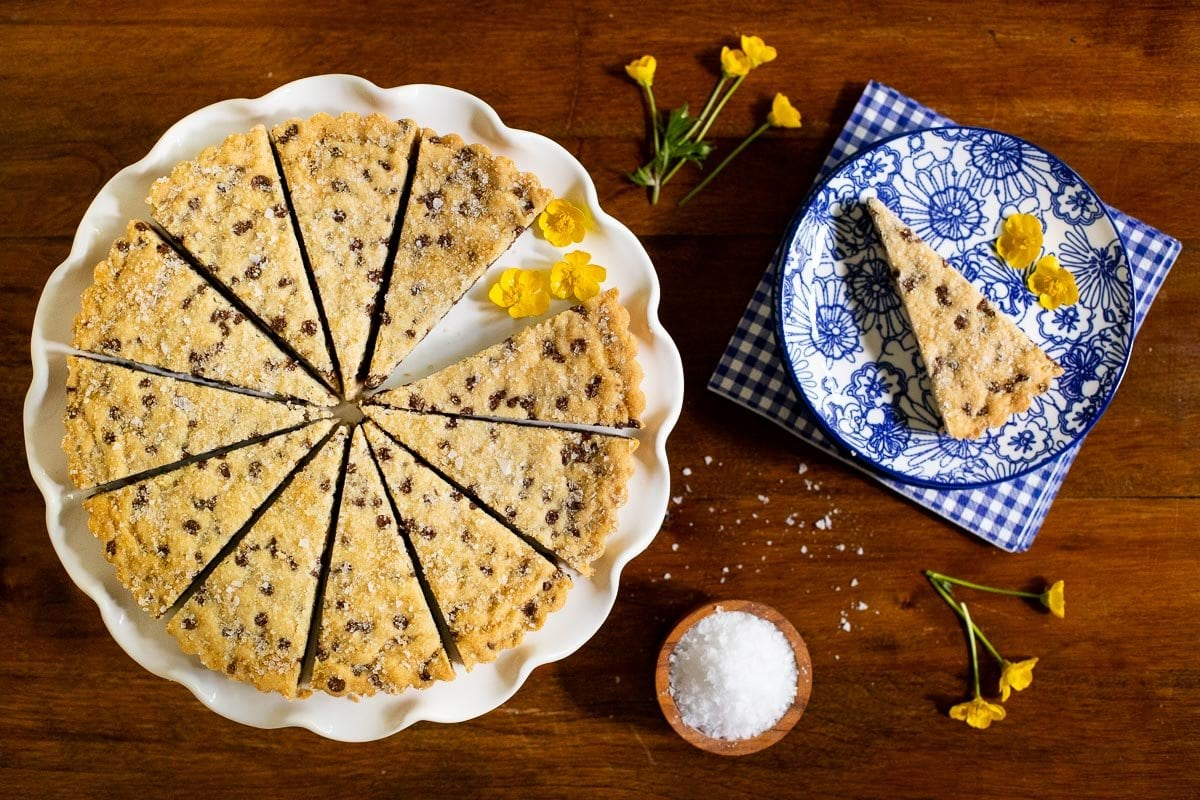 Horizontal overhead photo of a plate of Ridiculously Easy Chocolate Chip Shortbread on a wood table decorated with yellow buttercup flowers and garnished with sea salt.