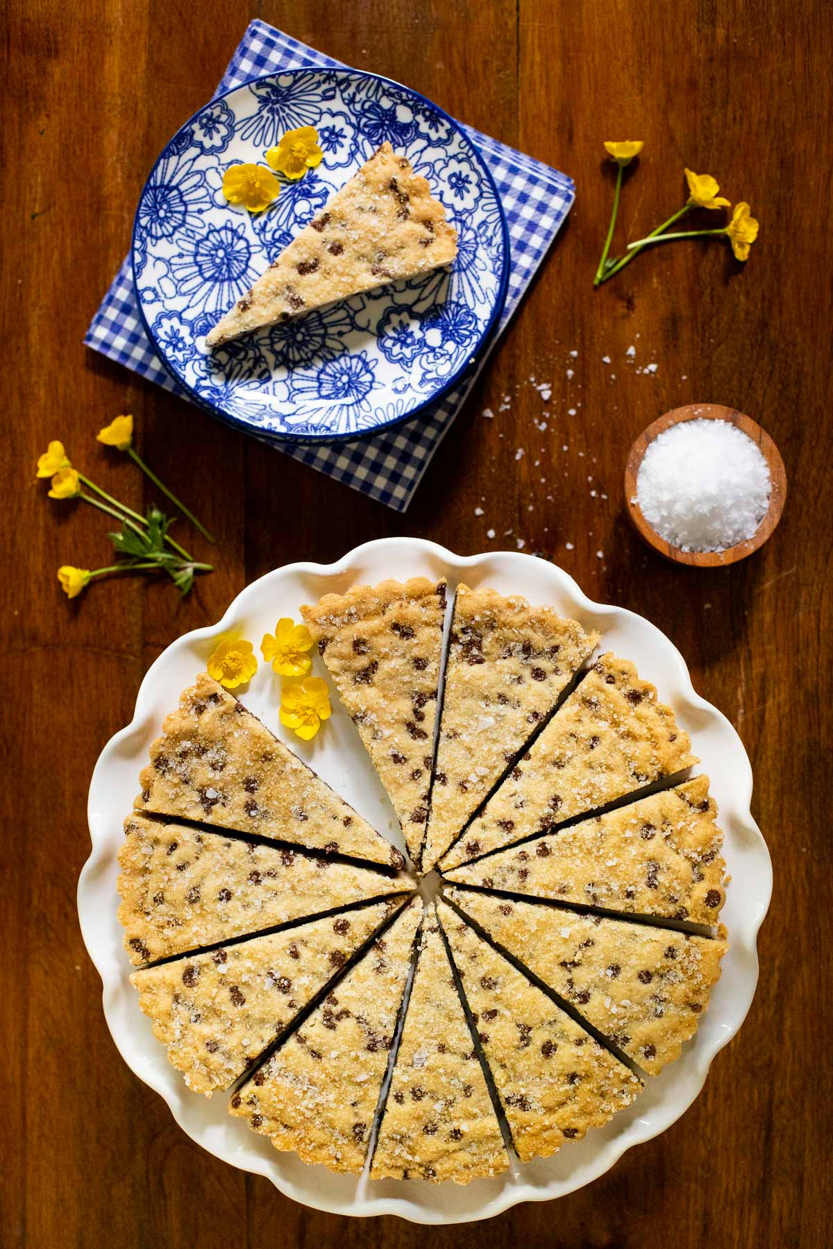 Vertical overhead picture of chocolate chip shortbread cut into wedges on a white plate