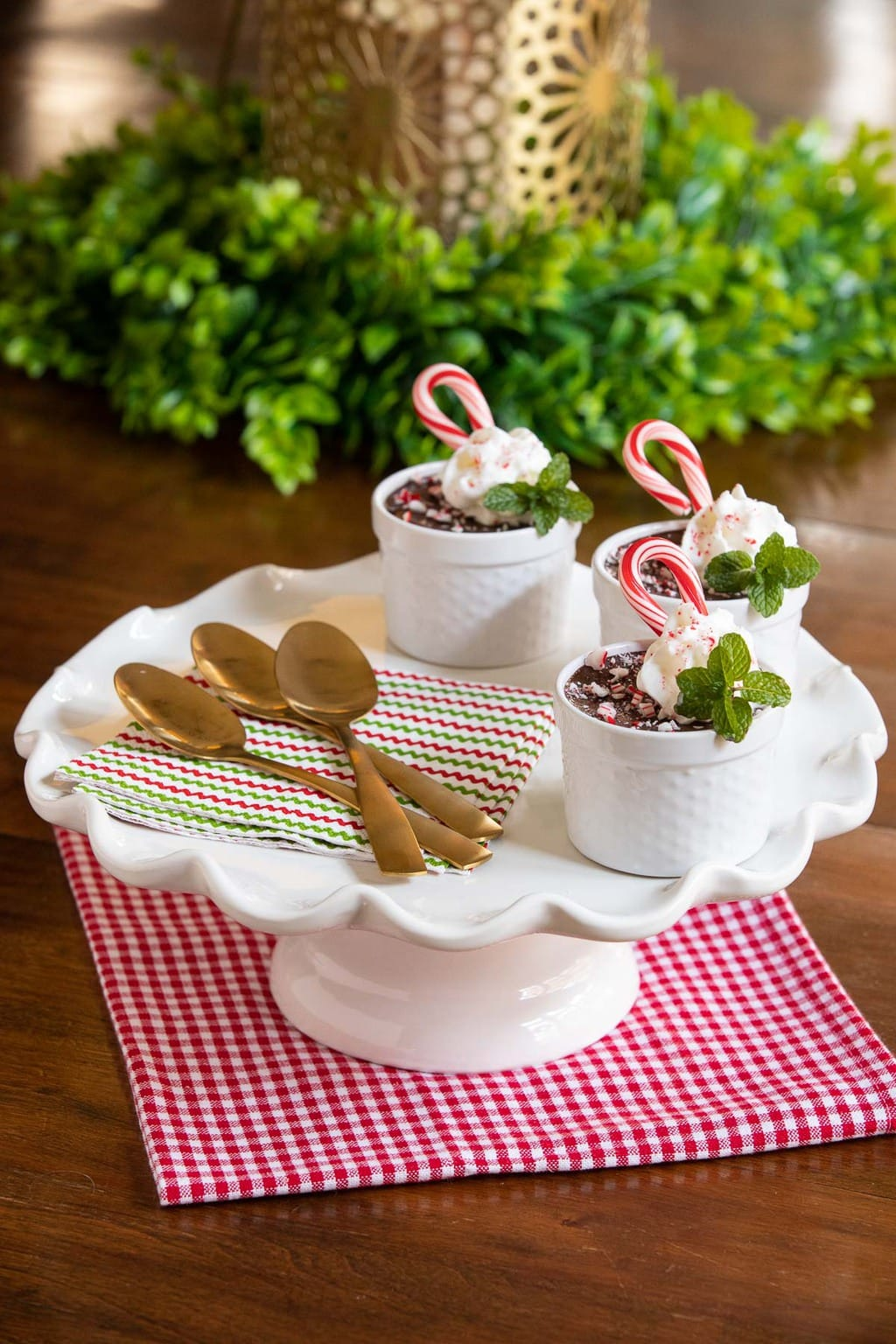 Vertical photo of cups of Ridiculously Easy Chocolate Peppermint Pots de Crème on a white scalloped pedestal plate on a wood table. The cups are garnished with candy canes, fresh mint and whipped cream.